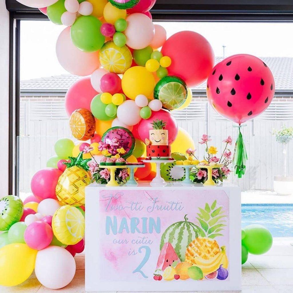 Mesa de postres con guirnalta orgánica colores tropicales