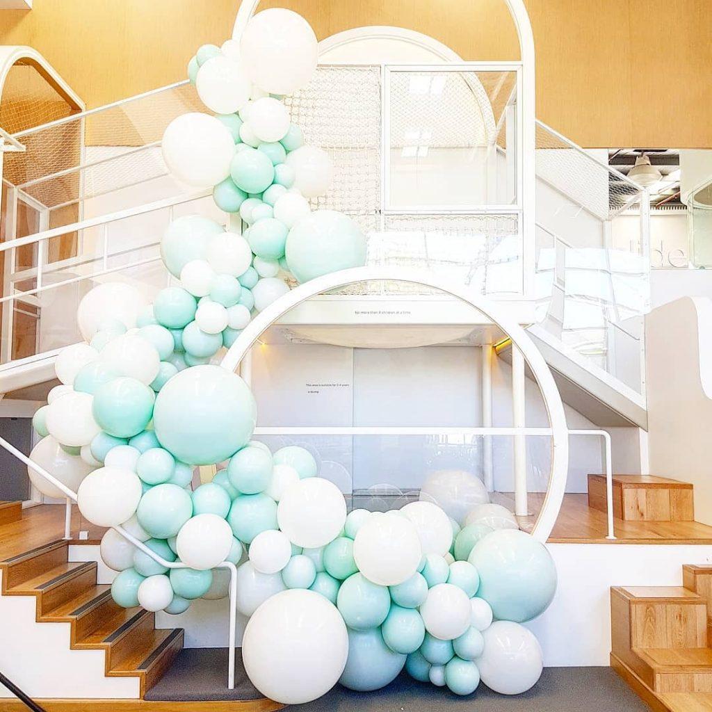 Decoración escalera con globos menta y blanco
