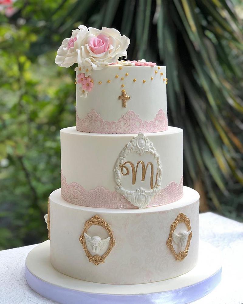 Pastel de niña para bautizo decoración sencilla tonos rosa y blanco con cruz dorada.
