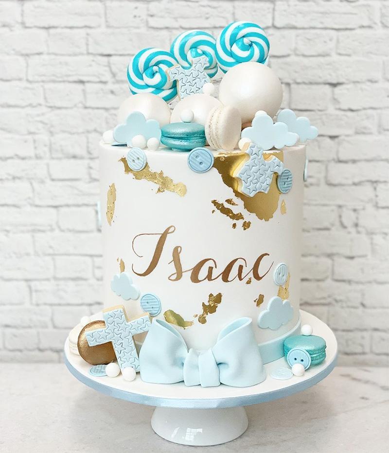 Torta de bautizo con hermosa decoración en tonos dorado y azul